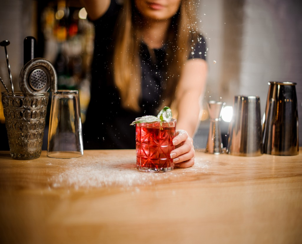 Barista Finishes Preparation Of R Cocktail With Mint Leaves By Adding A Bitter Of Powdered Sugar