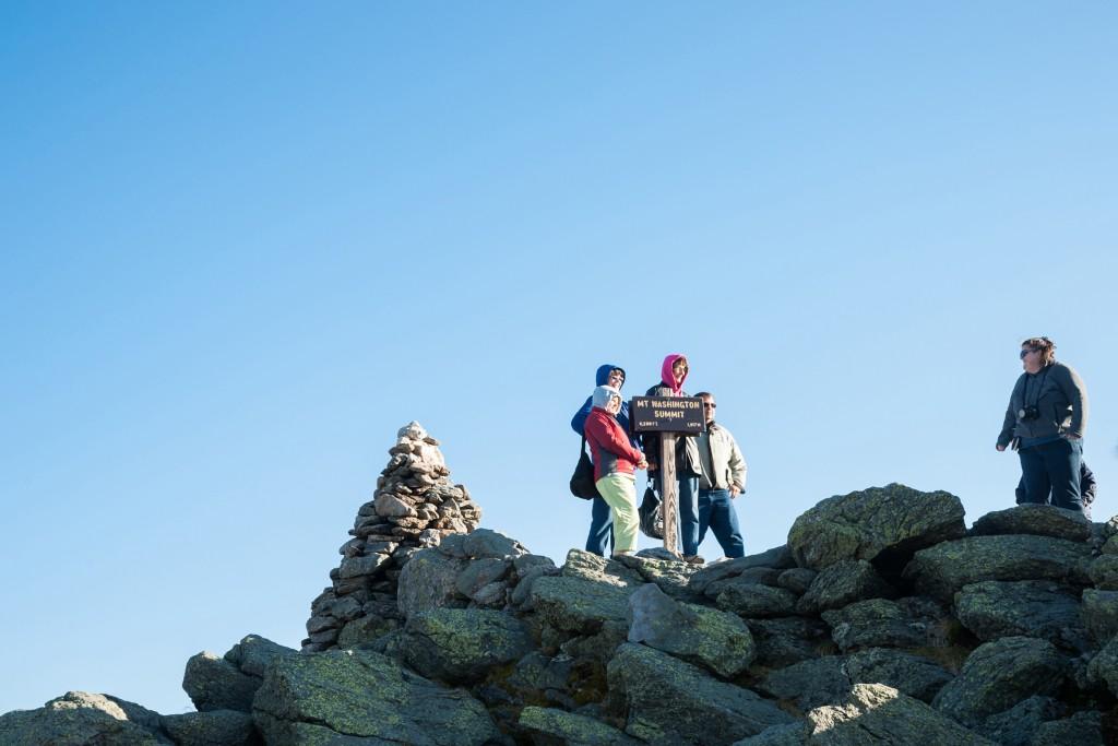 Group Of Travelers Stand On Mount Washington Peak